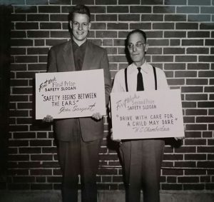 Black and white photo of two men holding up safety slogan signs